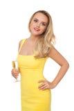 Mujer rubia que lleva el champán de consumición del vestido amarillo Foto de archivo