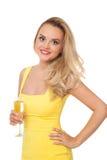 Mujer rubia que lleva el champán de consumición del vestido amarillo Fotos de archivo