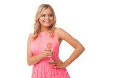 Mujer rubia que lleva el champán de consumición del vestido rosado Foto de archivo libre de regalías
