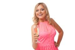 Mujer rubia que lleva el champán de consumición del vestido rosado Imagenes de archivo