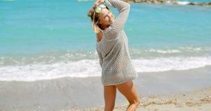 Mujer rubia que lleva a Grey Sweater Walking en la playa metrajes