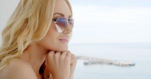 Mujer rubia que lleva las gafas de sol duplicadas almacen de video