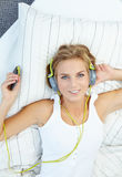 Mujer rubia que miente en cama mientras que música que escucha Foto de archivo libre de regalías