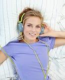 Mujer rubia que miente en cama mientras que música que escucha Fotos de archivo libres de regalías