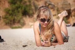 Mujer rubia que miente en la arena en la playa fotografía de archivo libre de regalías