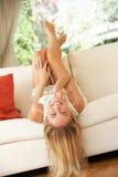 Mujer rubia que miente upside-down en el sofá Fotos de archivo libres de regalías