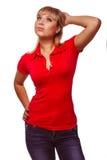 Mujer rubia que mira el chaleco y la mezclilla rojos para arriba de pensamiento Fotos de archivo