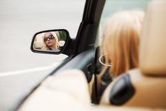 Mujer rubia que mira en el espejo de coche Fotos de archivo libres de regalías