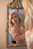 Mujer rubia que mira en el uno mismo en espejo Imágenes de archivo libres de regalías