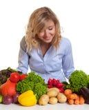 Mujer rubia que mira verduras frescas Foto de archivo