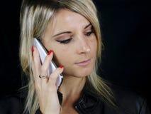 Mujer rubia que pasa una llamada de teléfono Imágenes de archivo libres de regalías