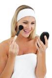 Mujer rubia que pone en maquillaje Imagen de archivo