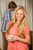 Mujer rubia que presenta con una taza con su novio detrás Fotos de archivo libres de regalías