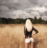 Mujer rubia que presenta en el campo. Visión trasera Fotografía de archivo libre de regalías