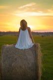 Mujer rubia que presenta en el tiempo de la puesta del sol en un campo Foto de archivo libre de regalías