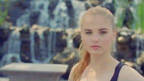 Mujer rubia que presenta en parque Retrato de la mujer joven cerca de la cascada almacen de video
