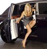 Mujer rubia que sale un coche de lujo Fotos de archivo