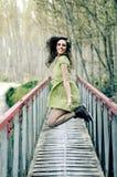 Mujer rubia que salta en un puente rural Imagen de archivo libre de regalías