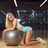 Mujer rubia que se arrodilla y que se inclina en bola gris del ejercicio Foto de archivo libre de regalías