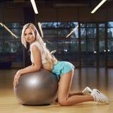Mujer rubia que se arrodilla y que se inclina en bola gris del ejercicio Imagen de archivo