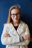 Mujer rubia que se inclina delante de una pared azul Imágenes de archivo libres de regalías