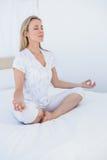Mujer rubia que se sienta en actitud del loto en cama Imagenes de archivo