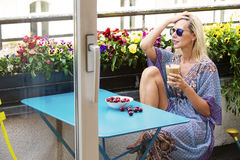 Mujer rubia que se sienta en balcón con café y cerezas Fotografía de archivo