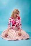 Mujer rubia que se sienta en el suelo imagenes de archivo