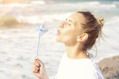 Mujer rubia que se sienta en la playa con un molinillo de viento Fotos de archivo