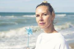 Mujer rubia que se sienta en la playa con un molinillo de viento Fotografía de archivo libre de regalías