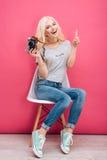 Mujer rubia que se sienta en la silla con la cámara de la foto Foto de archivo libre de regalías