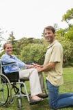 Mujer rubia que sonríe en silla de ruedas con el socio que se arrodilla por otra parte Fotos de archivo