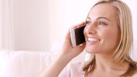 Mujer rubia que sonríe y que invita al teléfono almacen de metraje de vídeo