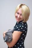 Mujer rubia que sostiene un gato británico del varón del shorthair Foto de archivo