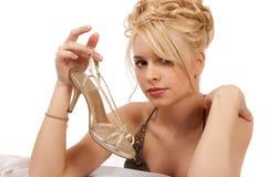 Mujer rubia que sostiene un zapato del oro imagen de archivo