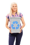Mujer rubia que sostiene una papelera de reciclaje Imagen de archivo