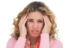 Mujer rubia que sufre con el dolor de cabeza que toca así sus templos Foto de archivo libre de regalías