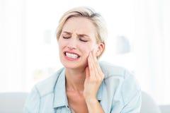Mujer rubia que tiene dolor de muelas Foto de archivo libre de regalías