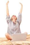 Mujer rubia que trabaja con la computadora portátil en cama Fotos de archivo libres de regalías