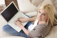 Mujer rubia que usa el ordenador portátil en el país en el sofá Foto de archivo libre de regalías