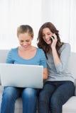 Mujer rubia que usa su ordenador portátil con su amigo que tiene una llamada de teléfono Foto de archivo libre de regalías