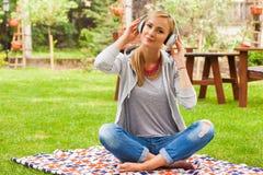Mujer rubia sensual joven con música que escucha de los auriculares en el PA Foto de archivo libre de regalías