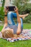 Mujer rubia sensual que miente en parque en la manta Ella está utilizando pizca Foto de archivo