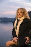 Mujer rubia sentada por el lago Fotografía de archivo
