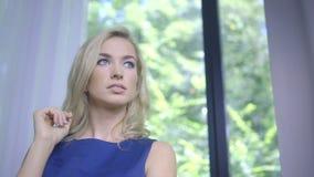 Mujer rubia sola que se coloca en la ventana que espera alguien almacen de video