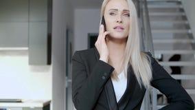 Mujer rubia sonriente de la Edad Media, director de gerente que tiene conversación del smartphone metrajes