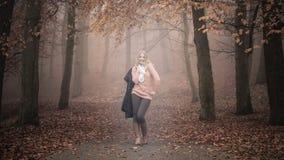 Mujer rubia sonriente de la moda con la chaqueta en parque Imagenes de archivo