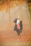 Mujer rubia sonriente de la moda en chaqueta en parque Foto de archivo
