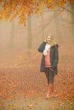 Mujer rubia sonriente de la moda en chaqueta en parque Imagen de archivo libre de regalías