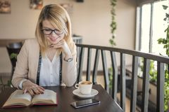 Mujer rubia sonriente de los jóvenes en un restaurante que lee un libro y que bebe el café fotos de archivo libres de regalías